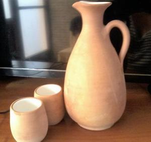 juego de jarra tallada de cerámica con dos vasos.