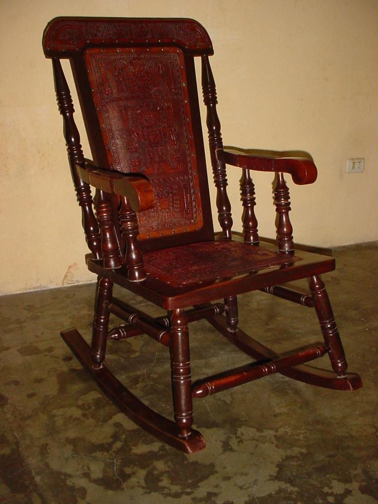 Silla mecedora en madera de cedro y tapiz de cuero tallado